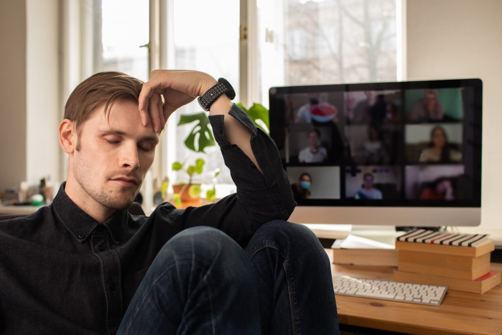 Man in front of screen closing eyes